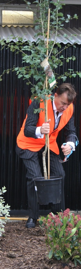 Duncan Bannatyne uses the Terra Firma trowel to tap a pot off the tree roots for  