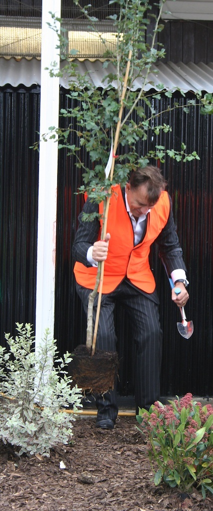 Duncan Bannatyne digs a hole and plants the tree for the BBC Children  